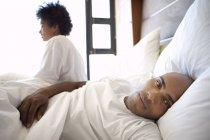 Hombre acostado en la cama - foto de stock
