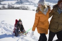 Man and woman pulling children on sled through snow — Stock Photo