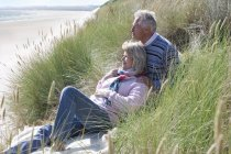 Senior couple sitting on beach and looking on seascape — Stock Photo