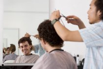 Closeup view of male barber cutting client's hair at barbershop — Stock Photo