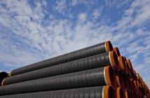 Vista de ángulo bajo de pila de tubos industriales sobre cielo azul nublado - foto de stock