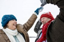 Senior couple playing together in snow — Stock Photo