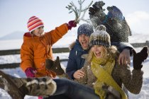 Son and daughter putting snow on man and woman — Stock Photo