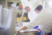 Chefs in restaurant kitchen cooking with soft focus background — Stock Photo