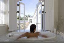 Woman in bubble bath against window — Stock Photo