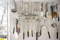 Kitchen utensils hanging from wall — Stock Photo