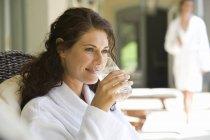 Жінки носять білий халат, питне скло води і посміхається — стокове фото