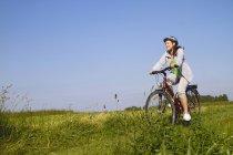 Jeune femme à vélo à travers champ — Photo de stock