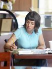 Front view of woman studying at restaurant — Stock Photo