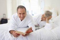 Homem, segurando o livro com sênior mulher deitada na cama — Fotografia de Stock