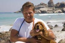 Человек обнимает собака на пляже и улыбается — стоковое фото