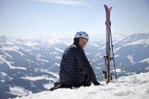 Зрелый человек, сидящий в снегу рядом с лыжи на горе — стоковое фото