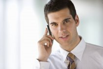 Businessman talking on cell phone and looking at camera — Stock Photo