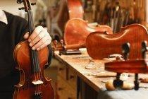 Скрипка чайник Холдинг скрипки в мастерской — стоковое фото