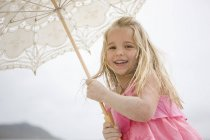Low angle view of young girl holding parasol — Stock Photo