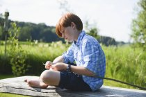 Boy carving wood on riverbank with defocussed background — Stock Photo