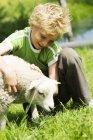 Фронтальний вид хлопчик, сидячи в траві і обіймати ягняти — стокове фото