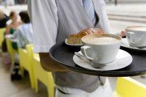 Cortar a imagem de garçom segurando a bandeja com café e croissant no terraço do café — Fotografia de Stock
