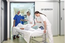 Doctor and nurses taking patient into operating room at hospital — Stockfoto