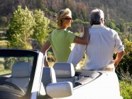 Rear view of couple by car looking at scenery — Stock Photo