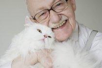 Vue de face de senior homme hugging blanc chat et souriant — Photo de stock
