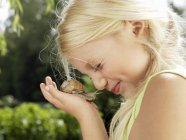 Side view of young girl looking at snail — Stock Photo