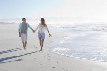 Coppia tenendosi per mano e camminare sulla spiaggia soleggiata — Foto stock