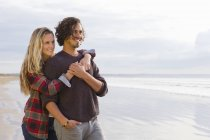 Portrait of smiling couple hugging and looking at view on sunny beach — Stock Photo