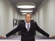 Uomo d'affari che posa in ufficio coridor — Foto stock