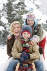 Portrait of mother and children sitting on snowsled — Stock Photo