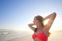 Smiling woman with arms raised behind head on sunny beach — Stock Photo