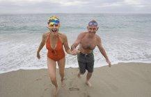 Зрелые пары в купальных костюмах рука об руку работать от моря — стоковое фото
