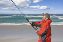 Senior man fishing on sunny beach — Stock Photo