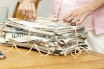 Mature female hands tying up pile of newspaper — Stock Photo