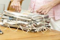 Mujer madura manos atar encima del montón de periódicos - foto de stock