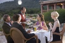 Waiter serving dishes to couples at restaurant balcony — Stock Photo