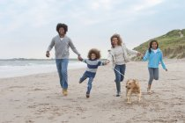 Happy family running along on beach with sea on background — Stock Photo