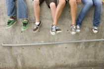 Small group of teenagers sitting on wall, low section — Stock Photo