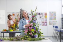 Smiling woman putting flowers into floral arrangement in classroom — Stock Photo