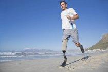 Inquadratura dal basso dell'uomo con la gamba artificiale in esecuzione sulla spiaggia — Foto stock