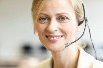 Portrait of mature woman wearing headset — Stock Photo