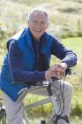 Portrait of mature man sitting on bicycle — Stock Photo