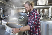 Male Brewery Worker Checking Fermentation Process In Steel Vat — Stock Photo
