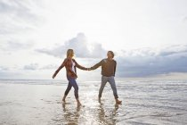 Cheerful couple walking and holding hands in ocean surf — Stock Photo