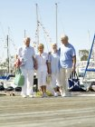 Two smiling mature couples walking on wooden jetty — Stock Photo