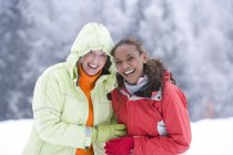 Portrait of happy women laughing in snow — Stock Photo