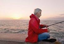 Mature homme mer pêche de jetée, coucher de soleil en arrière-plan — Photo de stock