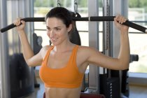 Vista della donna utilizzando attrezzature esercizi in palestra — Foto stock