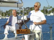 Mature man at wheel of boat with friend — Stock Photo