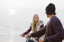 Smiling couple with bicycles looking at each one on ocean beach — Stock Photo